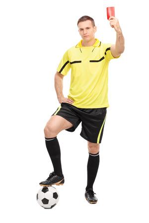 arbitro: Retrato de cuerpo entero de un estricto árbitro de fútbol de pie sobre una pelota y que muestra una tarjeta roja aislada en el fondo blanco Foto de archivo