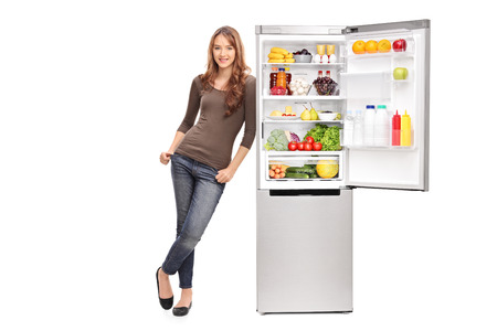 Full length portrait of a casual young girl leaning on an opened refrigerator full of food isolated on white background