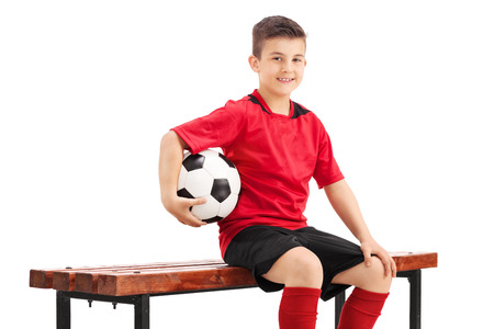 player bench: Proud junior football player posing seated on a wooden bench and holding a football in his hand isolated on white background