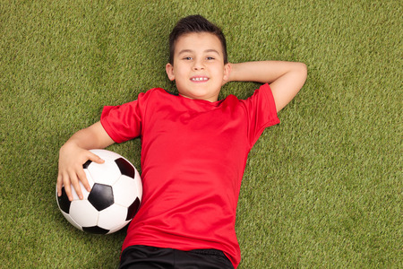 football jersey: Relaxed youngster in a red football jersey lying on a pitch, holding a football in his hand and looking at the camera Stock Photo