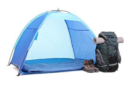 青いテント、緑のリュック、白い背景で隔離のテントの横に残っているブーツのペアのスタジオ撮影