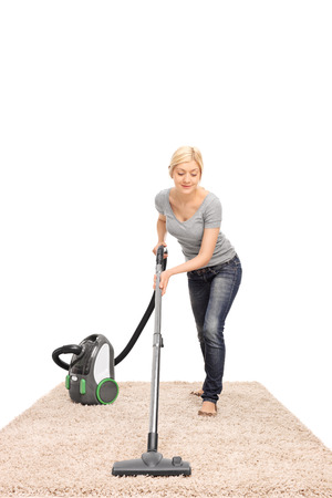 carpet clean: Full length frontal view of a young housewife vacuuming a beige colored carpet isolated on white background Stock Photo