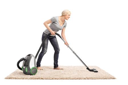 진공 청소기와 베이지 색 카펫을 진공 청소기로 청소하는 여자의 전체 길이 초상화 흰색 배경에 고립