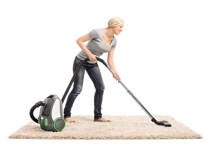 cleaning background: Full length portrait of a woman vacuuming a beige colored carpet with a vacuum cleaner isolated on white background Stock Photo