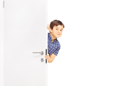 peek: Lovely little boy sneaking a peek behind a door and looking at the camera isolated on white background