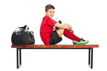 junior soccer: Junior soccer player in a red jersey, holding a ball and sitting on a wooden bench isolated on white background