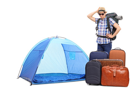 baffled: Baffled male tourist standing next to a tent and five huge briefcases isolated on white background