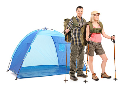 Male and female hiker standing next to a blue tent and carrying hiking equipment isolated on white background photo