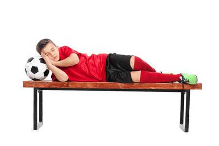 Studio shot of a kid in a football uniform sleeping on a bench Zdjęcie Seryjne