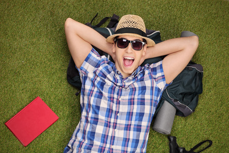 Excited male hiker lying on his backpack in a grass field and looking at the camera Stock Photo