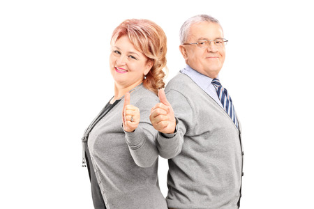 happy couple white background: Confident and happy mature couple giving thumbs up and looking at camera isolated on white background
