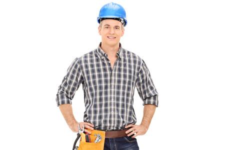 albañil: Chico confidente construcción en uniforme que llevaba el casco azul y posando aislados sobre fondo blanco