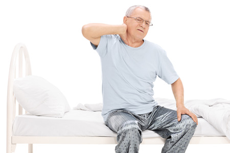 senior man on a neck pain: Senior man in pajamas feeling pain in his neck seated on a bed isolated on white background