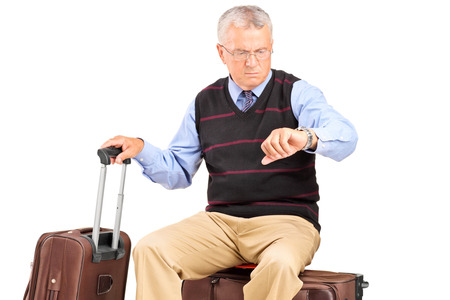 late 60s: Senior tourist checking the time seated on his luggage isolated on white