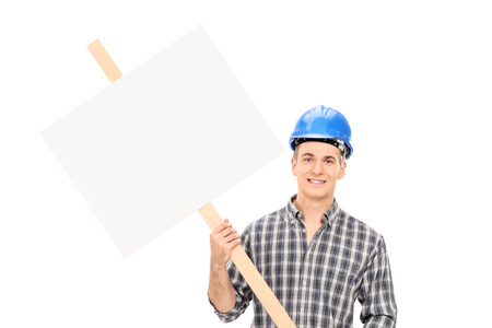 Smiling male construction worker in uniform and blue helmet holding a blank sign isolated on white background photo