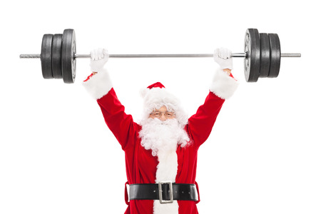 heavy weight: Smiling Santa Claus lifting a heavy barbell and looking at camera isolated on white background