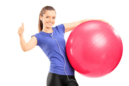posing  agree: Smiling young woman holding a red exercise ball and giving a thumb up isolated on white background