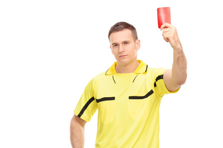 arbiter: Strict football referee standing and showing a red card isolated on white background