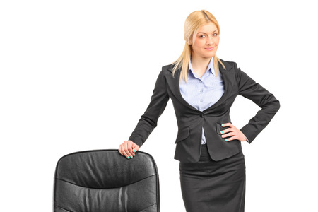 formal clothes: Young blond businesswoman wearing black suit and standing by an office chair isolated on white background Stock Photo