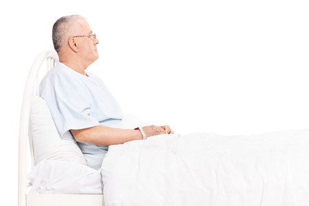bored man: Studio shot of a senior patient in a hospital gown, lying in a bed and looking around isolated on white background Stock Photo