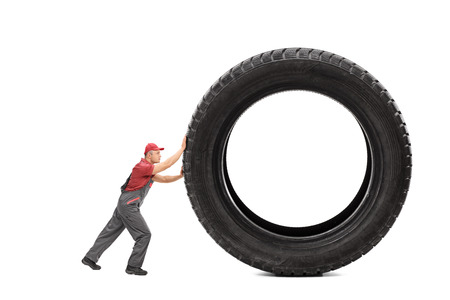 jumpsuit: Full length portrait of a mechanic in a gray jumpsuit pushing a giant black tire isolated on white background