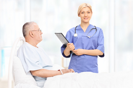 Female healthcare professional holding a clipboard and standing next to a mature patient who is lying in hospital bed Stock Photo
