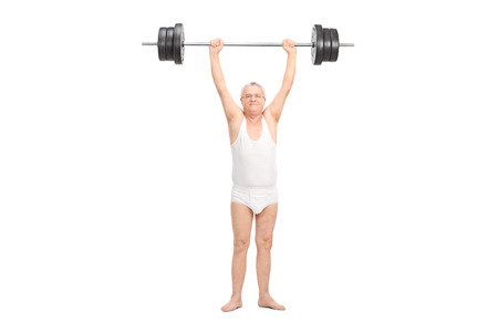 Studio shot of a semi-dressed senior lifting a heavy barbell and looking at the camera isolated on white background Stock Photo