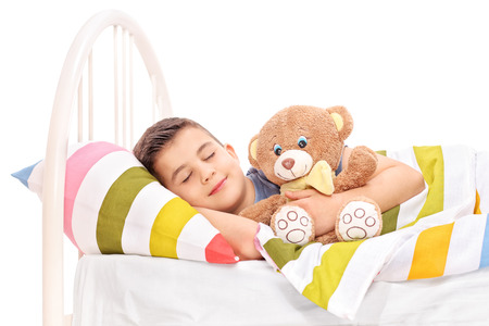 Cute little kid sleeping with a teddy bear covered with a blanket in bed isolated on white background photo