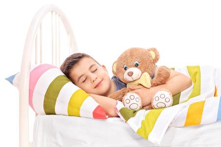 enfant qui dort: Gamin mignon dormir avec un ours en peluche recouvert d'une couverture dans le lit isolé sur fond blanc Banque d'images
