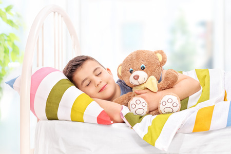 Lovely boy sleeping with a teddy bear in a comfortable bed covered with a striped multicolored blanket at home photo