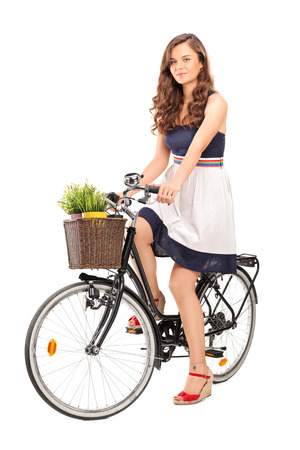 the basket: Beautiful young woman posing seated on a black bicycle with a basket in the front, carrying two flowerpots isolated on white background Stock Photo