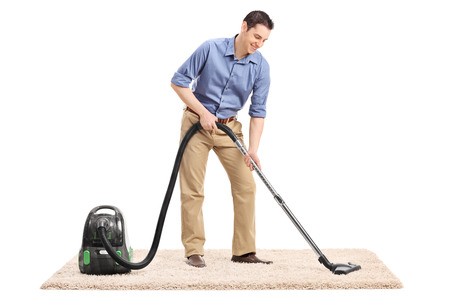 cleaning background: Full length portrait of a young man cleaning a carpet with a vacuum cleaner isolated on white background