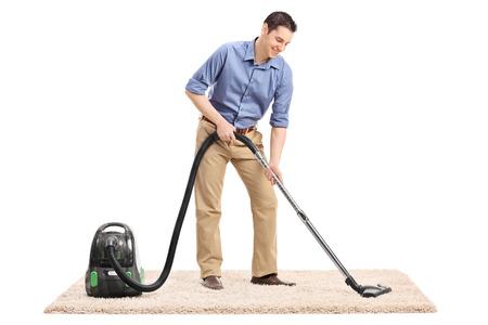 personal de limpieza: Retrato de cuerpo entero de un joven limpiar una alfombra con un aspirador aislado en fondo blanco