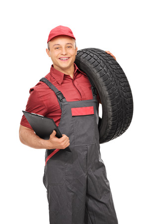 jumpsuit: Vertical shot of a male manual worker in a gray jumpsuit holding a clipboard and a tire isolated on white background