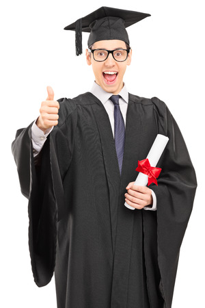 overjoyed: Vertical shot of an overjoyed graduate student in a graduation gown, holding a diploma and giving a thumb up isolated on white background