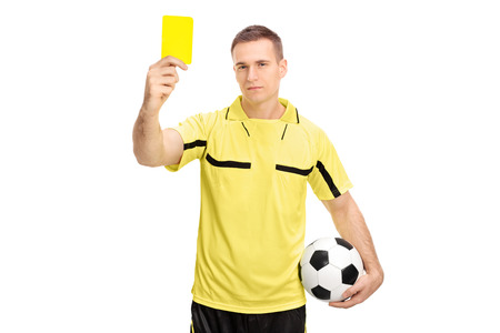 yellow card: Young male football referee holding a ball and showing a yellow card isolated on white background Stock Photo