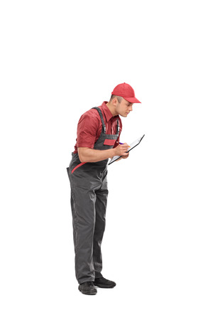 clipboard isolated: Full length portrait of a mechanic in a gray jumpsuit writing down notes on a clipboard isolated on white background