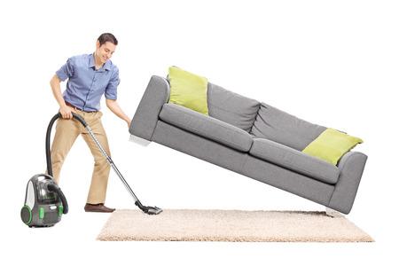 personal de limpieza: Alegre joven que levanta un sof� y la limpieza debajo de ella con el aspirador aislado en fondo blanco