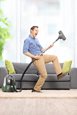 Delighted young guy playing guitar on the vacuum cleaner wand in front of a gray soda at home