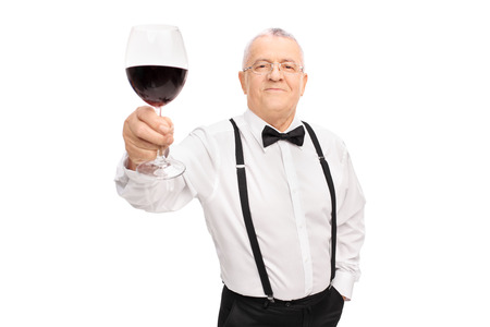 toasting wine: Elegant senior gentleman proposing a toast with a glass of red wine and looking at the camera isolated on white background Stock Photo