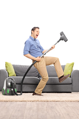 Excited young guy pretending to be playing guitar on the vacuum cleaner wand in front of a gray sofa isolated on white background