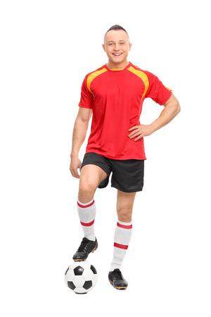 amateur: Retrato de cuerpo entero de un joven jugador de fútbol masculino de pie sobre una pelota y mirando a la cámara aislada en el fondo blanco