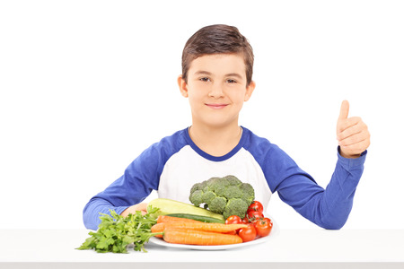 posing  agree: Little kid sitting on a table with a plate full of fresh vegetables and giving a thumb up isolated on white background