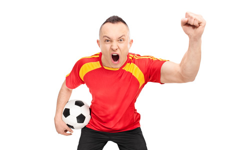 delirious: Ecstatic young sports fan in a red football jersey holding a football and cheering isolated on white background