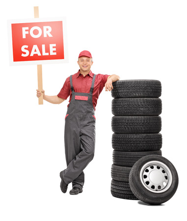Full length portrait of a cheerful male mechanic standing by a pile of tires and holding a big red for sale sign isolated on white background photo