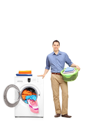 Full length portrait of a young man standing next to a washing machine full of clothes, holding a green laundry basket and looking at the camera isolated on white background Reklamní fotografie