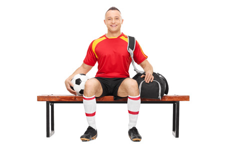 Studio shot of a young guy in football uniform holding a football and carrying a sports bag seated on a wooden bench photo