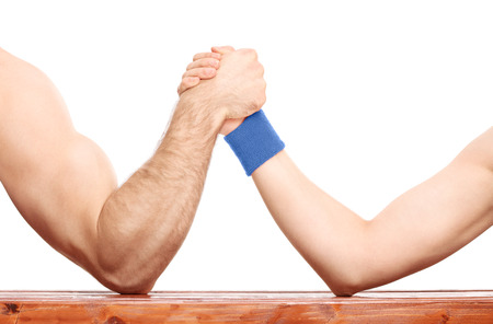 Close-up on an uneven arm wrestling contest between a muscular arm and a skinny one isolated on white background Фото со стока