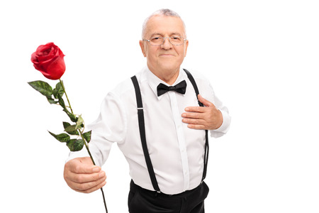 Romantic senior gentleman handing a red rose flower towards the camera isolated on white background