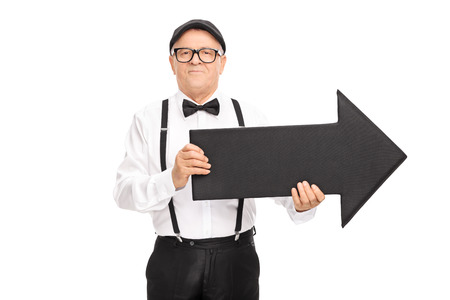 Senior gentleman with black bow-tie and suspenders holding a big black arrow pointing right isolated on white background
